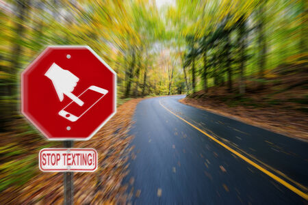 handheld device: A red stop sign with a symbol of a hand texting on handheld smartphone device and the words stop texting written on a sign bellow   Stock Photo