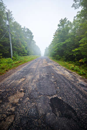 pot hole: Potholes on a country road on a foggy day