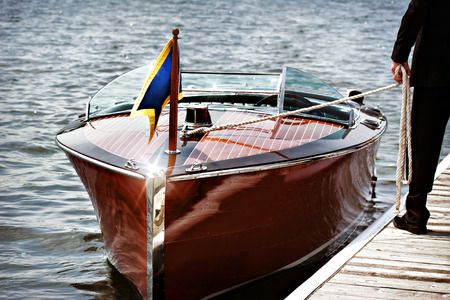 bow of boat: A docked wooden motor boat.  A man stands on the dock holding the mooring line. Stock Photo