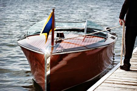 bateau de course: Un bateau à moteur en bois amarré. Un homme se tient sur le quai se tenant par la ligne de mouillage.