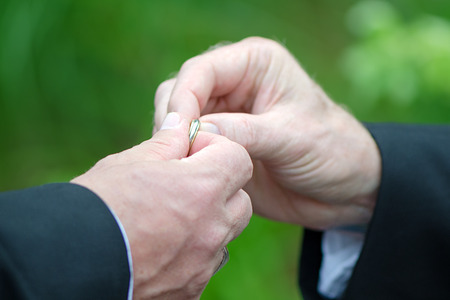 A man handing over a wedding ring to the groom photo
