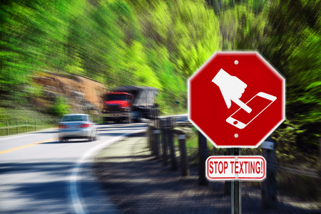 Stop sign with a symbol of a handheld device and the words Stop Texting printed on it.  Imagens