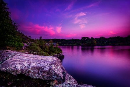 muskoka: A violet sunset over a calm lake with trees on a rocky shoreline.