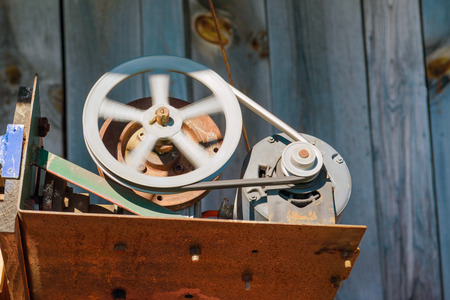 driven: A spinning flywheel driven by an electric motor and belt