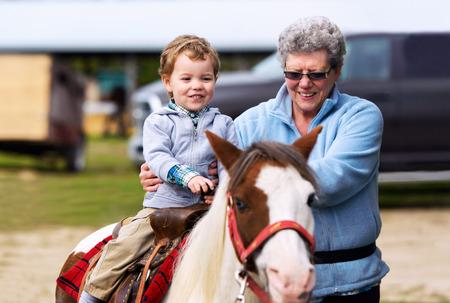 Een gelukkige jongen rijdt op een pony voor de eerste keer met zijn grootmoeder ondersteunen hem aan zijn zijde. Stockfoto