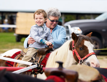 pretty pony: A happy boy rides a pony for the first time with his grandmother supporting him by his side.  Stock Photo