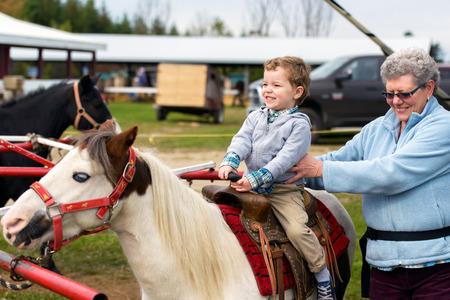 Ein glücklicher Junge reitet auf einem Pony zum ersten Mal mit seiner Großmutter ihm Unterstützung an seiner Seite. Standard-Bild - 28838250