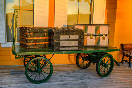 waggon: Three vintage baggage containers sit atop a green vintage wagon.  Stock Photo