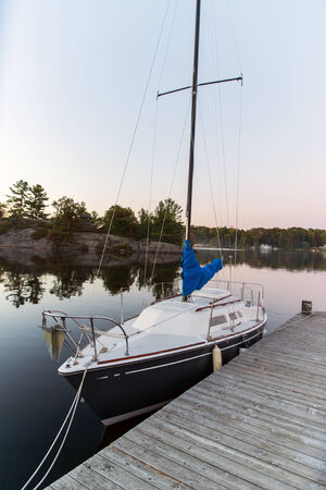 A small sailboat sits docked on a calm lake during the evening.  photo
