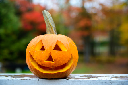 A close up shot of a happy jack-o-lantern sitting on a rail of a deck during the day with colorful autumn trees in the background.