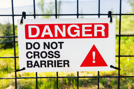 barrier: A sign posted on a wire fence with the words Danger Do Not Cross Barrier on it.