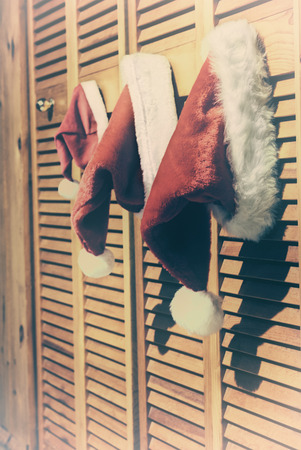closet door: Two adult and one small sized santa hats hanging from a closet door.