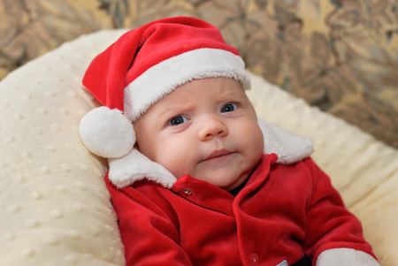 A close up portrait of a baby in a Santa suit with a grumpy expression.