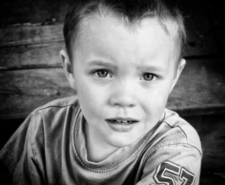 Een close up van een jonge jongen met een serieuze blik. Verwerkt in zwart en wit