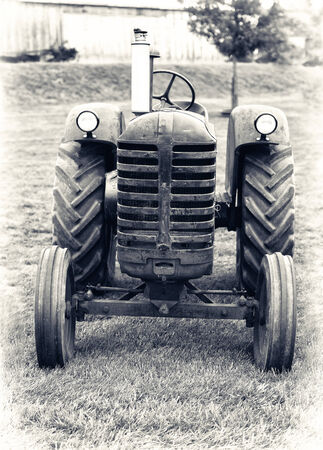 old farm: A front view of an old farm tractor sitting in a field.  Lightly Toned. Stock Photo