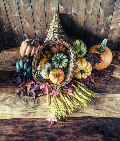 A cornucopia with squash, gourds, pumpkins, wheat and leaves on an old antique table.