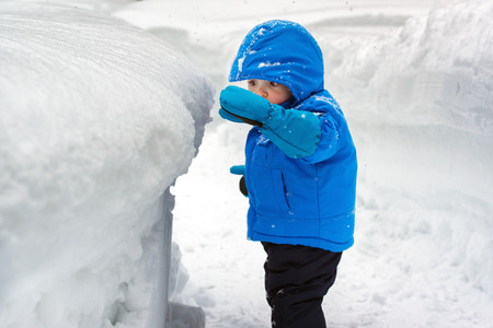 On a snowy day a little boy stands outside looking at a deep snow bank which is as tall as he is.  He is reaching out to touch the top of the snow bank.