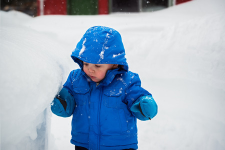 On a snowy day a little boy is standing next to a deep snowbank which is as tall as he is.   He is touching the snowbank with his glove.
