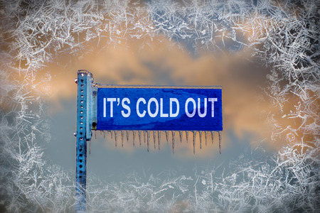 A close up of a frozen blank blue street sign containing the text Its Cold Out! is covered in ice and icicles against a cloudy sky.  There is a border of frost surrounding the image.