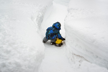 bank records: A little boy dressed in a snowsuit is crouched down outside playing with a yellow toy dump truck in a cleared snow path and there are deep snow banks on either side of him.