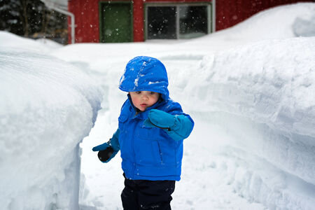 On a snowy day a little boy is standing next to a deep snow bank which is as tall as he is.   He is looking at snow on his glove. Stock Photo