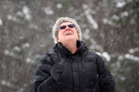 A close up portrait of a senior woman looking up on a snowy day. photo