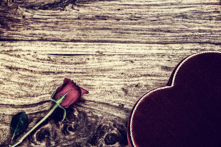 A single rose and heart shaped box of chocolates against a wooden rustic . photo