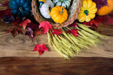 cuerno de la abundancia: Un cuerno de la abundancia con la calabaza, calabazas, calabazas, trigo y hojas sobre una vieja mesa de cosecha antigua. Sala de espacio de la copia.