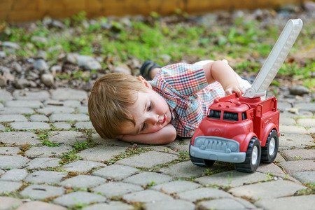 fire truck: Boy and Toy Fire Truck series 5.  A toddler laying down on the ground playing with a toy fire truck outside in the summer.   Stock Photo