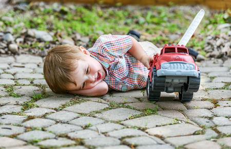 Boy and Toy Fire Truck series 6.  A toddler laying down on the ground smiling and playing with a toy fire truck outside in the summer.