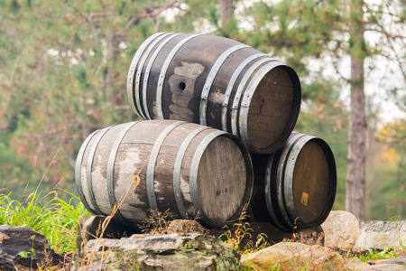 Three wine barrels stacked outside on their sides.