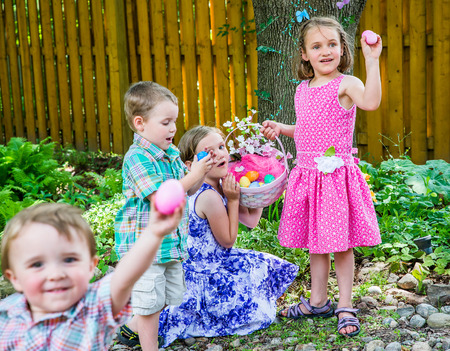Two girls hold an Easter egg basket full of eggs; one of the girls holds up a pink Easter egg. A happy boy standing beside the girls looks down at a blue egg in his hands he has just found.  A little boy smiles looking at the camera holding up a pink egg