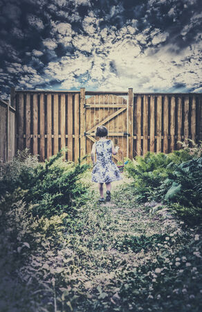 fenced in: A little girl walks down a path toward a wooden gate in a fenced in garden looking for Easter eggs during an Easter egg hunt.  There are clouds in a darkened sky above.  Room for copy space.