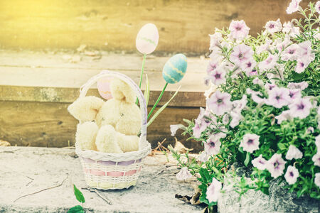 A plush yellow Easter bunny sits in a basket with three eggs in a garden setting outside during the spring season.  Filtered for a retro, vintage look. photo