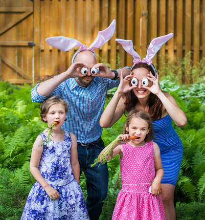 A funny family portrait on Easter of a mother and father wearing bunny ears and holding up silly eyes made from eggs as their children pose eating carrots outside in a garden during the spring season.