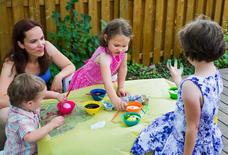 painting decorating: Family painting & decorating eggs outside in a springtime garden setting.  Mother smiles as girl shows her green dyed hand, while children have fun color dying their Easter eggs.  Part of a series.