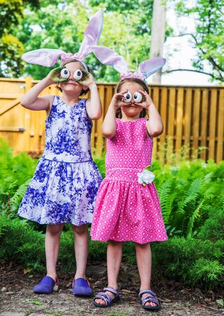 A funny portrait of two girls having fun on Easter wearing bunny ears and holding up silly eyes made from eggs outside in a garden during the spring season.  Part of a series. Standard-Bild