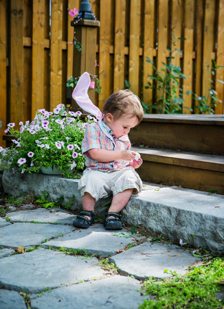 finds: Boy with bunny ears resting on his shoulders spends a quiet moment for himself, and sits on a step peeling an egg he finds during an Easter hunt in the spring season in a beautiful garden setting.  Part of a series.
