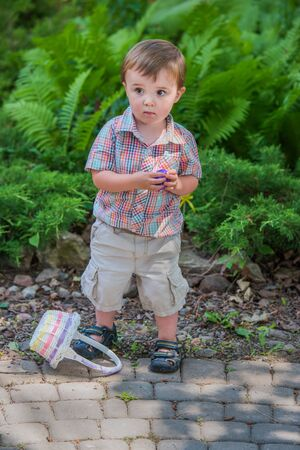finds: A happy boy with his Easter basket on the ground holds a purple Easter egg he finds during an Easter egg hunt activity in the spring season in a beautiful garden setting. Part of a series.