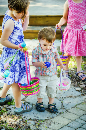 A little boy holds a blue egg to put in his basket he found during an Easter egg hunt in a garden during the spring.  A girl in a dress holding a colorful basket stands beside him.  Part of a series. Stock fotó