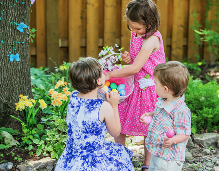 Two little girls hold a basket with flowers and color dyed Easter eggs outside in a beautiful garden in the spring.  A little boy holding pink eggs walks by and looks at the basket.  Part of a series.