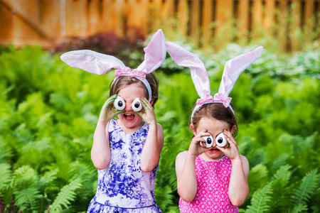 A funny portrait of two girls having fun on Easter wearing bunny ears and holding up silly eyes made from eggs outside in a garden during the spring season.  Part of a series. Stock Photo