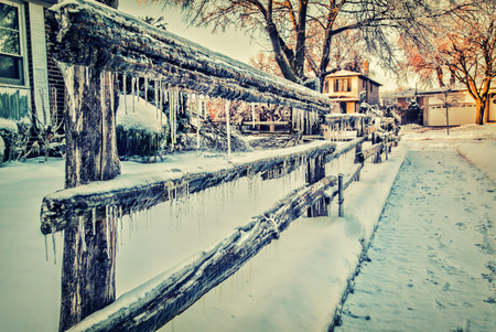 neighborhood: A wooden fence covered in ice in an urban neighborhood after an ice storm.  Filtered for a retro, vintage look. Stock Photo