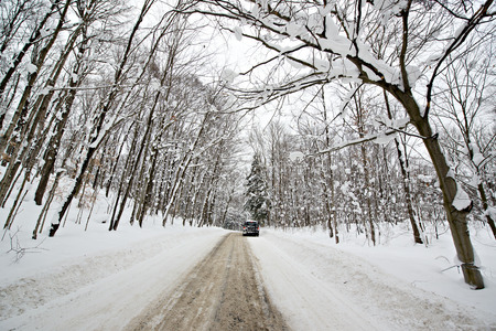 A car is parked down a rural road covered in snow with deep snow banks and snow covered trees on either side of the road during the winter season.