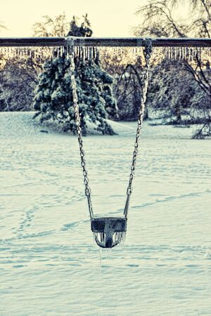 ice storm: A swing in a playground covered in thick ice and icicles after an ice storm.