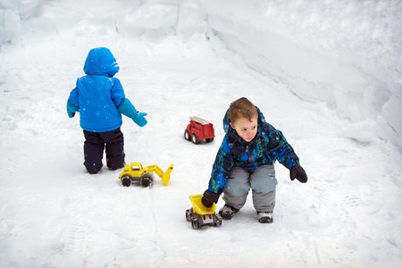 snowbanks: Two boys are playing outside with toy trucks in the snow during a snowfall during the winter season.  There are deep snowbanks around them.