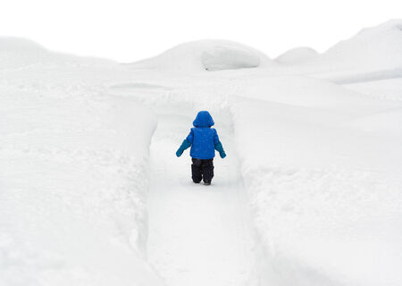 bank records: Back view of a little boy in a snowsuit walking through a snowy path with deep snow banks on either side.   Stock Photo