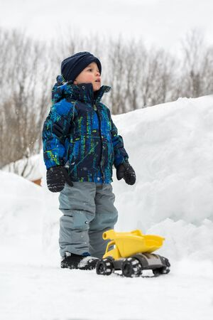 A little boy dressed in a snowsuit is outside standing beside a yellow toy dump truck in a cleared snow path and there is a deep snowbank beside of him.