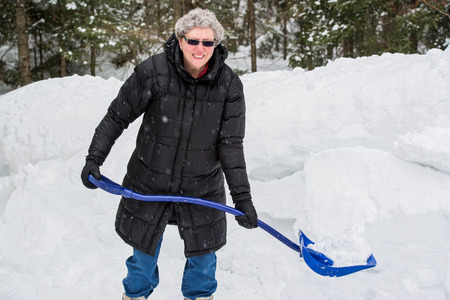 A portrait of a healthy elderly woman holding a shovel full of snow on a cold snowy day.