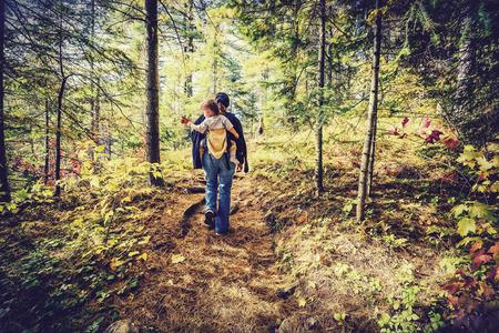 Eine Mutter ist das Wandern auf einem Pfad in einem Wald mit ihrem Baby in einem Hinterträger während der Herbstsaison. Gefiltert, um retro geben, verblaßten Blick. Standard-Bild - 36570381